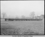 Augustana World War I military stand in line on open field at 38th Street and 7th Avenue