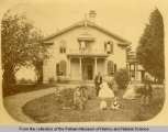 Mr. and Mrs. C. E. Putnam and family posing on the lawn of their home.