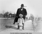 Elmer McCraney and daughter Harriet on the boardwalk at Main Street (now Cody Road) and Walnut Street