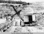 Steam shovel filling railroad cars in quarry at Dewey Portland Cement